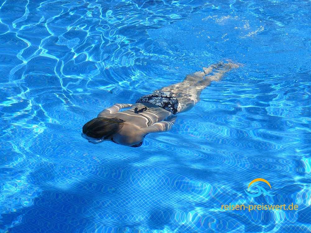 Im Urlaub im Pool schwimmen und tauchen