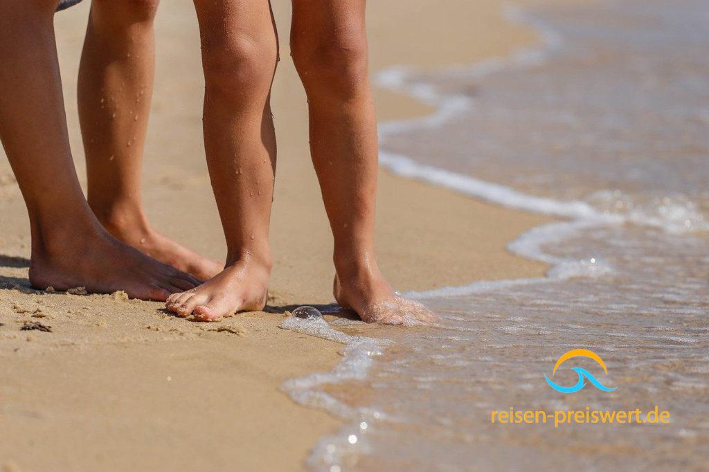 Urlaub mit der Familie am Strand - barfuß im Sand am Meer