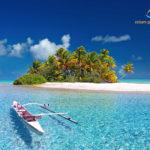 Ein Boot vor einen einsamen Insel mit Palmen in französisch Polynesien